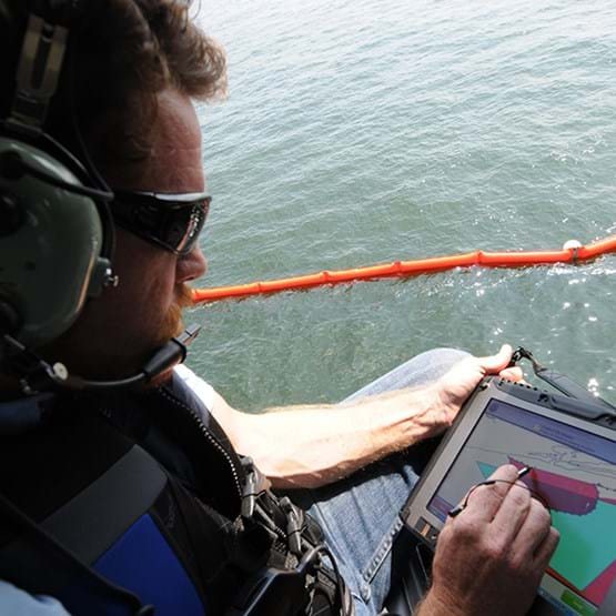 man in helicopter mapping oil spill