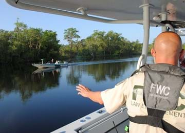FWC officer in vessel waving at boaters on river