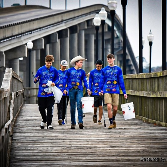 Five male students, wearing their blue team fishing shirts, walking down a pier next to an overpass working on collecting trash for their conservation project